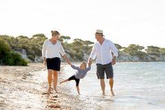 Młody szczęśliwy matki i ojca odprowadzenie z małą córką na plaży w rodzinnego wakacje pojęciu Zdjęcia Stock
