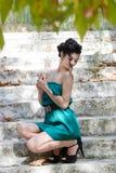 Mody szczupła kobieta jest ubranym zielonego bez ramiączek krótkiego smokingowego obsiadanie na starych i brudnych cementowych sc Obraz Royalty Free