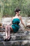 Mody szczupła kobieta jest ubranym zielonego bez ramiączek krótkiego smokingowego obsiadanie na starych i brudnych cementowych sc Obrazy Stock