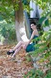 Mody szczupła kobieta jest ubranym zielonego bez ramiączek krótkiego smokingowego siedzącego chodniczek, Zdjęcia Stock