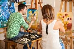 Młodzi dorosli maluje przy szkołą artystyczną Zdjęcia Royalty Free