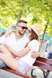 Młodzi ludzie na ławce w parku Zdjęcie Royalty Free
