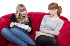 Młodzi piękni blondyny i czerwone z włosami dziewczyny martwią się o liście dalej Fotografia Stock