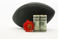 Moeda americana do dólar e flor vermelha na frente do footba preto Fotografia de Stock Royalty Free