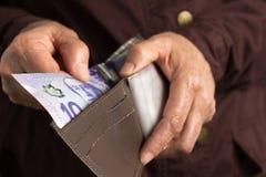 Moeda canadense Dólares Pessoa aposentada idosa que paga no dinheiro fotografia de stock royalty free