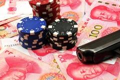Moeda chinesa com as microplaquetas da arma e de pôquer Foto de Stock