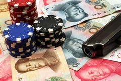 Moeda chinesa com as microplaquetas da arma e de pôquer Fotografia de Stock Royalty Free