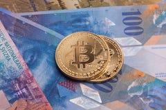 Moeda cripto da moeda de Bitcoin sobre cédulas dos francos suíços Fotografia de Stock