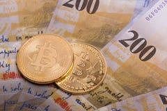 Moeda cripto da moeda de Bitcoin sobre cédulas dos francos suíços Fotografia de Stock Royalty Free