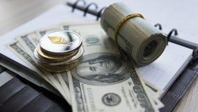 Moeda cripto de Ethereum sobre 100 biils do dólar no bloco de notas Lucro de minar moedas criptos Mineiro com dólares Foto de Stock