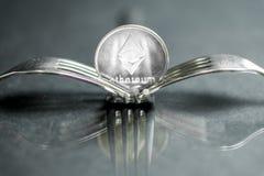 Moeda cryptocurreny de Ethereum colocada entre forquilhas com reflexão, forquilha dura fotografia de stock