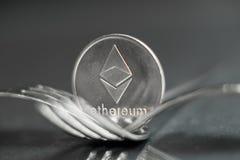 Moeda cryptocurreny de Ethereum colocada entre forquilhas com reflexão, forquilha dura imagem de stock