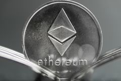 Moeda cryptocurreny de Ethereum colocada entre forquilhas com reflexão, forquilha dura foto de stock royalty free