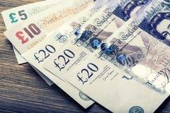 Moeda da libra, dinheiro, cédula Moeda inglesa Cédulas BRITÂNICAS de valores diferentes empilhadas em se Imagens de Stock