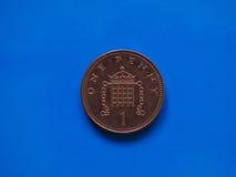 1 moeda da moeda de um centavo, Reino Unido sobre o azul Imagens de Stock