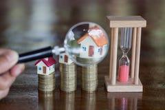 A moeda da pilha e o gráfico de barra com crescem, a lupa que procura por uma casa nova, empréstimo para bens imobiliários ou par imagens de stock
