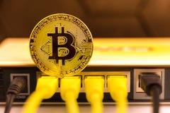 Moeda de Bitcoin na parte de trás do roteador fotos de stock royalty free