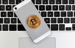 Moeda de Bitcoin no telefone esperto com o teclado de computador no backgr Imagem de Stock