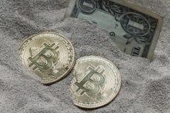 Moeda de Bitcoin vista enterrada parcialmente na areia do silicone junto com uma cédula de um dólar fotografia de stock royalty free