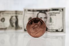 Moeda de bronze de Dogecoin perto dos dólares Imagens de Stock