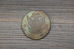 Moeda de cobre do russo do vintage com águia dois-dirigida, 5 kopeks de Catherine The Great a segunda em um fundo de madeira escu Foto de Stock Royalty Free