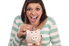 Moeda de colocação adolescente étnica no banco Piggy no branco Imagens de Stock