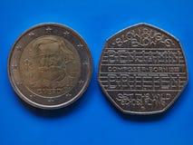Moeda de dois Euros e de 20 moedas de um centavo sobre o azul Foto de Stock Royalty Free