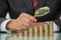 Moeda de Holding Magnifier On do homem de negócios na mesa Fotos de Stock Royalty Free