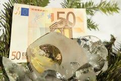 Moeda de ouro de Bitcoin congelada ao meio em uma parte de gelo em um fundo branco com ramos de árvore do Natal e no euro 50 de E fotografia de stock