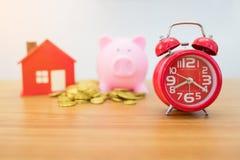 Moeda de ouro, casa pequena, piggybank e despertador Imagem de Stock Royalty Free