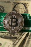 Moeda de prata do bitcoin com dólares e cartão-matriz do computador, mineração do cryptocurrency e investimento fotografia de stock