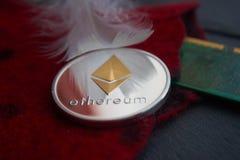 A moeda de prata de Ethereum que encontra-se em lãs vermelhas surge fotografia de stock