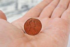 Moeda de um centavo ereta da vista detalhada na mão masculina Fotos de Stock Royalty Free