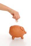 Moeda deixando cair da mão no banco piggy Fotografia de Stock
