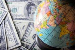 Moeda, dinheiro e globo do mundo Fotografia de Stock Royalty Free