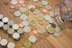Moeda do baht tailandês fora do frasco de vidro Fotografia de Stock Royalty Free