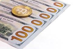 A moeda do bitcoin encontra-se em cem notas de dólar dos E.U. Cinco cédulas encontram-se em um fundo branco, formando uma figura  Fotografia de Stock Royalty Free