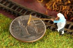 A moeda do dinheiro pôs sobre a cena modelo diminuta da estrada de ferro foto de stock