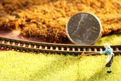 A moeda do dinheiro pôs sobre a cena modelo diminuta da estrada de ferro fotos de stock royalty free