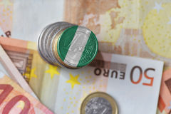 Moeda do Euro com a bandeira nacional de Nigéria no euro- fundo das cédulas do dinheiro Fotografia de Stock
