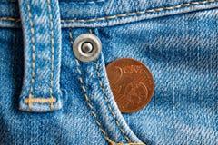 Moeda do Euro com uma denominação do euro- centavo dois no bolso de calças de brim azuis velhas gastas da sarja de Nimes Fotos de Stock