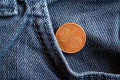 Moeda do Euro com uma denominação do euro- centavo 2 no bolso de calças de brim azuis velhas da sarja de Nimes Foto de Stock