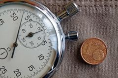Moeda do Euro com uma denominação de 1 euro- centavo e cronômetro no contexto bege velho das calças de brim - fundo do negócio Foto de Stock Royalty Free