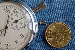 Moeda do Euro com uma denominação de 50 euro- centavos e de cronômetro em contexto azul gasto da sarja de Nimes - fundo do negóci Imagens de Stock