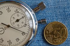 Moeda do Euro com uma denominação de 50 euro- centavos e de cronômetro no contexto azul da sarja de Nimes - fundo do negócio Imagem de Stock