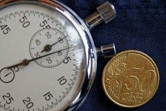 Moeda do Euro com uma denominação de 50 euro- centavos e de cronômetro no contexto azul obsoleto da sarja de Nimes - fundo do neg Fotos de Stock