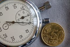 Moeda do Euro com uma denominação de 50 euro- centavos e de cronômetro no contexto cinzento da sarja de Nimes - fundo do negócio Foto de Stock