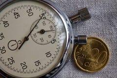 Moeda do Euro com uma denominação de 20 euro- centavos e de cronômetro no contexto de linho branco - fundo do negócio Fotos de Stock Royalty Free