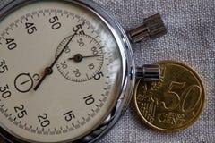 Moeda do Euro com uma denominação de 50 euro- centavos e de cronômetro no contexto de linho branco - fundo do negócio Foto de Stock Royalty Free