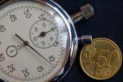 Moeda do Euro com uma denominação de 50 euro- centavos e de cronômetro no contexto preto da sarja de Nimes - fundo do negócio Imagens de Stock